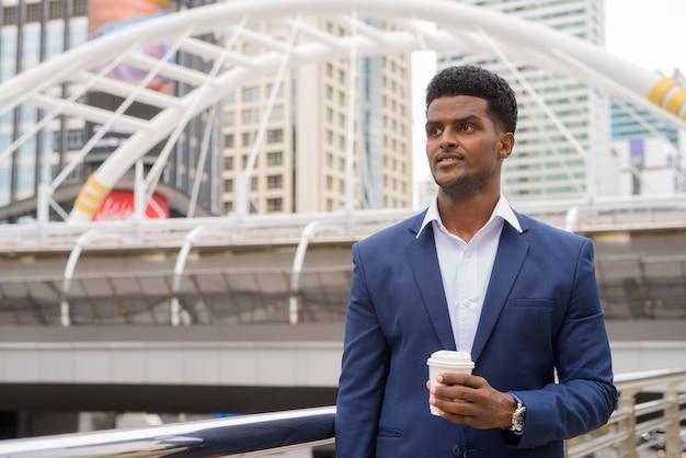 屋外で考えて保持しているアフリカのビジネスマンの肖像画は、コーヒーカップ、水平方向のショットを奪う