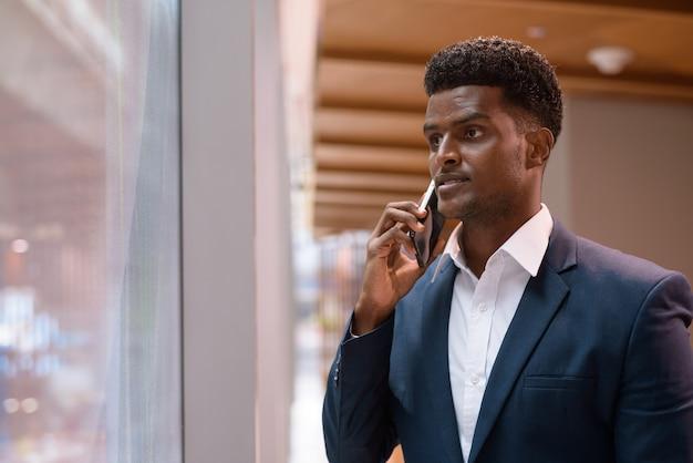 창 옆에 서서 실내, 수평 샷 휴대 전화에 얘기하는 아프리카 사업가의 초상화