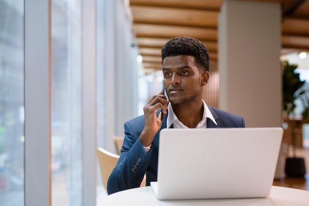 노트북 컴퓨터를 사용하고 창을 통해보고있는 동안 커피 숍에서 휴대 전화로 얘기하는 아프리카 사업가의 초상화, 가로 샷