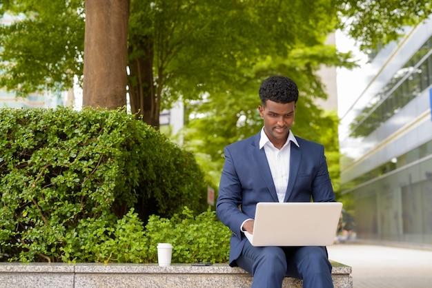 앉아, 가로 샷 동안 도시에서 야외에서 랩톱 컴퓨터를 사용하는 아프리카 사업가의 초상화