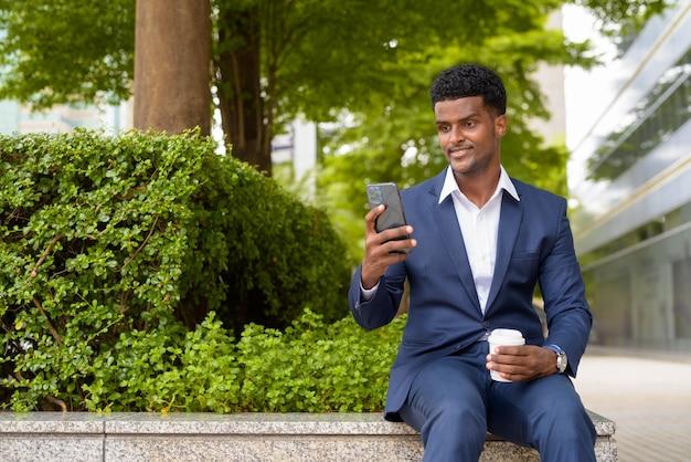 電話を使用して持ち帰りのコーヒーカップを持っているアフリカのビジネスマンの肖像画、水平ショット