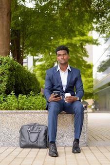 電話を使用し、携帯電話を使用しながら都市の屋外でコーヒーカップを持ち帰るアフリカのビジネスマンの肖像画