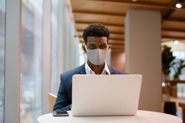 얼굴 마스크를 착용하고 커피 숍에서 랩톱 컴퓨터를 사용하는 아프리카 사업가의 초상화, 가로 샷