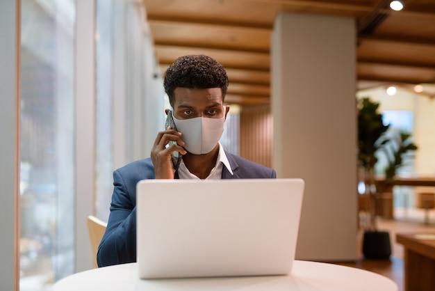 얼굴 마스크를 착용하고 커피 숍에서 휴대 전화로 이야기하는 동안 랩톱 컴퓨터를 사용하는 아프리카 사업가의 초상화, 가로 샷