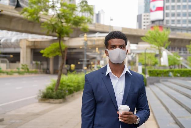 屋外でフェイスマスクを着用し、持ち帰りのコーヒーカップ、水平ショットを保持しているアフリカの実業家の肖像画