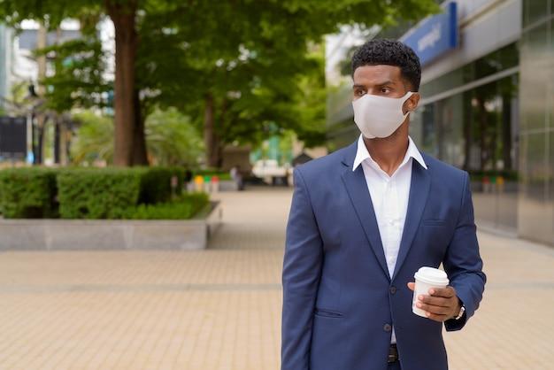 屋外でフェイスマスクを着用し、考えながらコーヒーカップをテイクアウト、水平ショットを保持しているアフリカのビジネスマンの肖像画