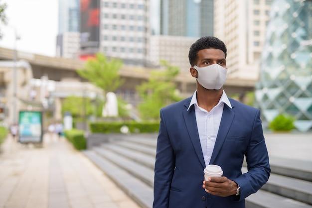 街の屋外でフェイスマスクを着用し、持ち帰りのコーヒーカップ、水平ショットを保持しているアフリカの実業家の肖像画