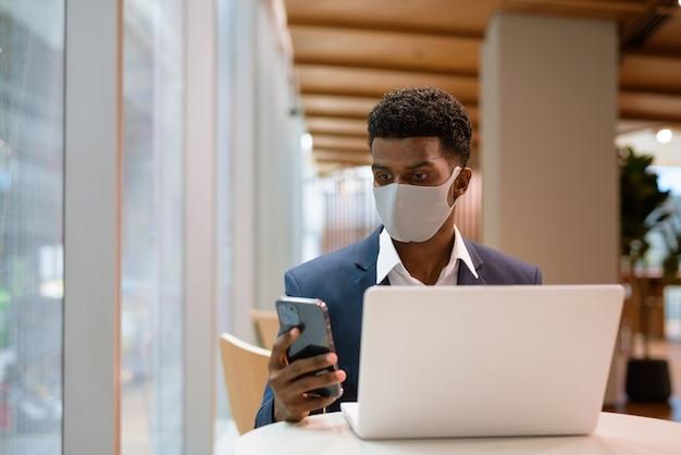 커피 숍에서 노트북 컴퓨터와 휴대 전화를 사용하는 동안 얼굴 마스크를 쓰고 아프리카 사업가의 초상화, 가로 샷