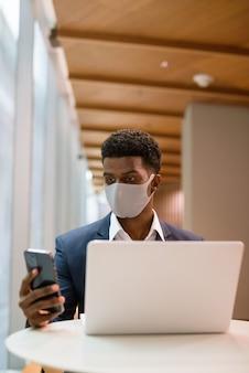 커피 숍 세로 샷에서 랩톱 컴퓨터와 휴대 전화를 사용하는 동안 얼굴 마스크를 쓰고 아프리카 사업가의 초상화