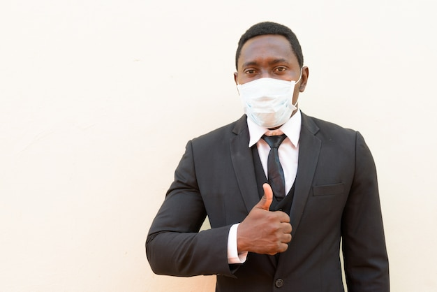 白い背景に対して親指をあきらめてマスクを持つアフリカの実業家の肖像画