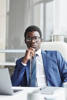 Портрет африканского уверенно бизнес-лидера в очках, сидя на своем рабочем месте