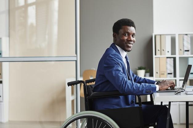 オフィスでラップトップコンピューターで入力しながら笑っているアフリカの障害のあるビジネスマンの肖像画