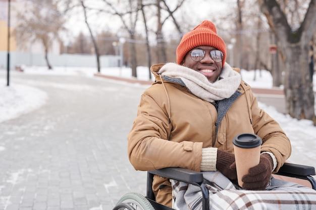 Портрет африканского инвалида в инвалидной коляске, улыбаясь в камеру, попивая горячий кофе в парке