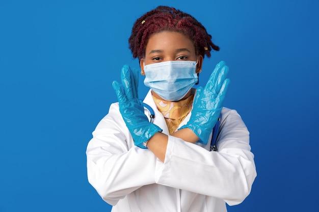 Портрет африканской женщины-врача в лабораторном халате с маской для лица и стетоскопом на синем фоне