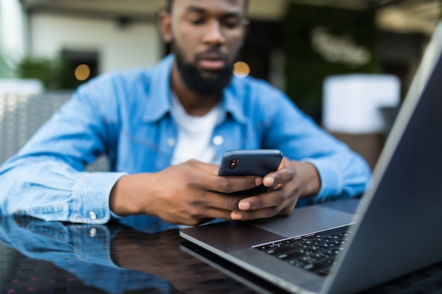 카페에서 테이블에 그 앞에서 노트북으로 전화로 얘기하는 아프리카 남자의 초상화