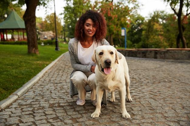 Портрет африканской леди гулять с собакой в парке