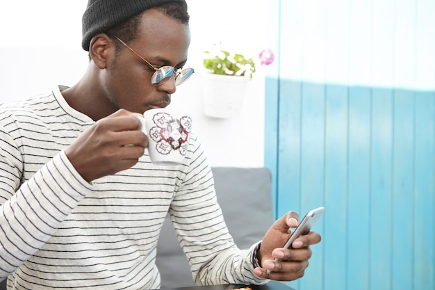 Портрет африканского мужчины в стильной одежде, держащего кружку, пьющего свежий кофе, просматривающего интернет и проверяющего ленту новостей в социальных сетях, использующего сотовый телефон во время завтрака в кафе с уютными местами