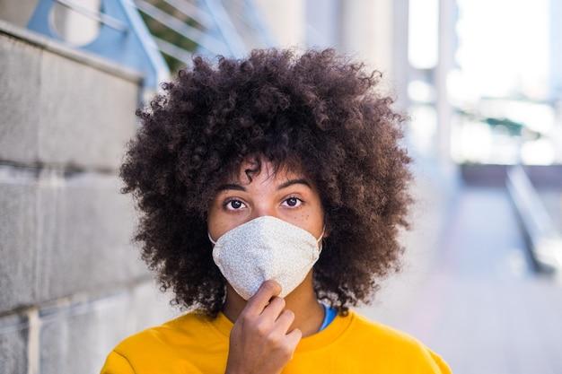 Covid-19がカメラを見るのを防ぐために医療用マスクを着用しているアフリカまたはアメリカの若い女性の肖像画。背景の街と通り