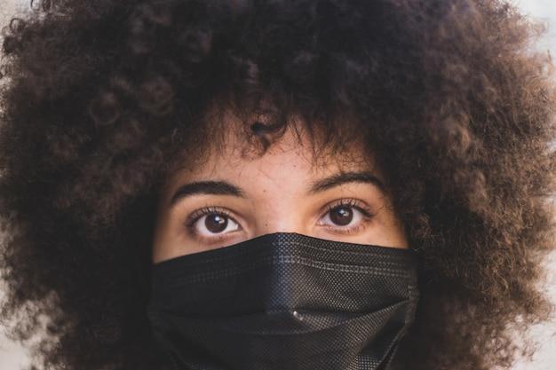 Covid-19がカメラを見るのを防ぐために医療用マスクを着用しているアフリカまたはアメリカの若い女性の肖像画