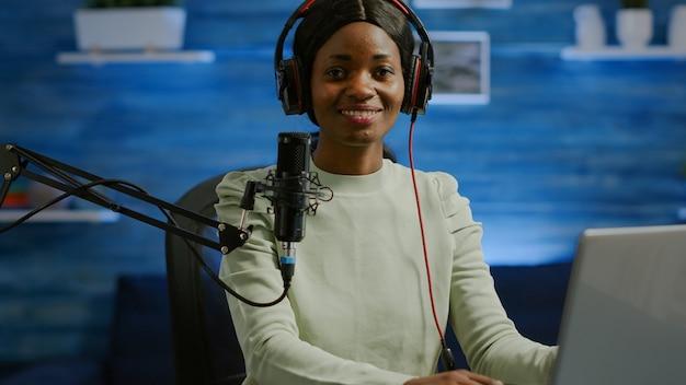 홈 스튜디오 팟캐스트에서 라이브 비디오를 시작하기 전에 카메라를 바라보며 웃고 있는 아프리카 블로거의 초상화. 콘텐츠 제작자 동영상 블로거 여성이 소셜 미디어용으로 온라인 콘텐츠를 스트리밍하는 방송을 녹화하고 있습니다.