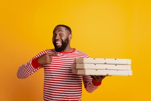 Портрет африканского студента-курьера держит стопку коробок для пиццы, указывая пальцем, продвигая рекламу