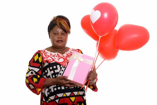 Портрет африканской женщины, держащей воздушные шары и подарок