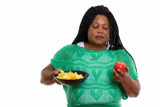 Портрет африканской женщины, держащей чипсы и яблоко