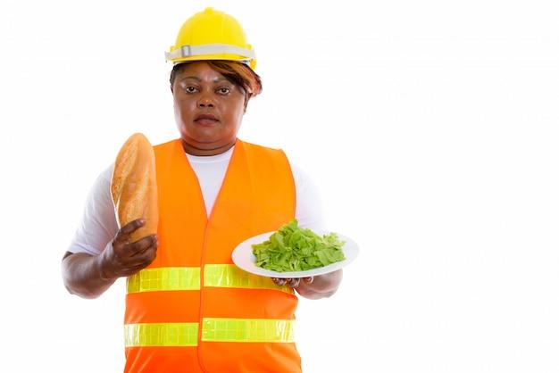 ヘルメットをかぶって食べ物を保持しているアフリカの女性の肖像画