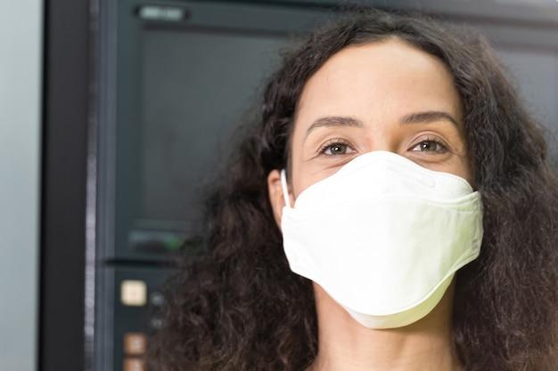 フェイスマスクを身に着けているアフリカの女性の肖像画。工場で働く女性。