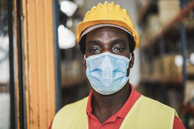保護マスクを着用しながら倉庫内のアフリカの労働者の男性の肖像画-男の目に焦点を当てる