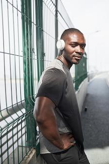 駅でワイヤレスヘッドフォンでトレーニングしながらカメラを見ているアフリカの若いアスリートの肖像画...