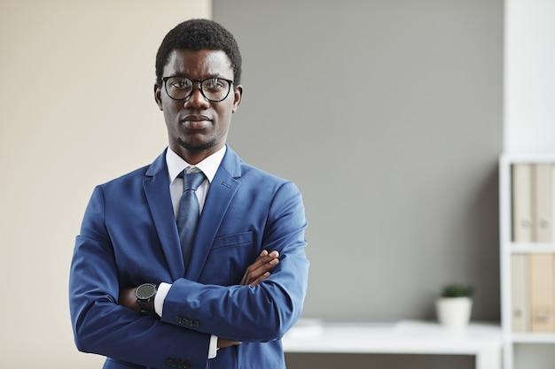 Портрет африканского молодого бизнесмена в очках и в строгой одежде, стоящего со скрещенными руками