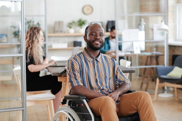 彼の同僚とオフィスで働いている間車椅子に座って、カメラに笑みを浮かべてアフリカの青年実業家の肖像画