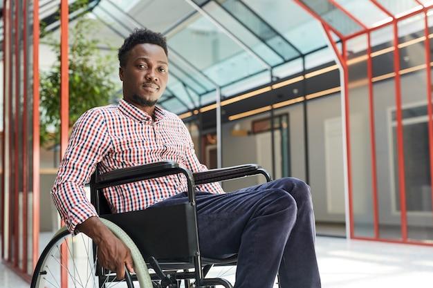 オフィスビルで車椅子に座っているアフリカの若い障害者の肖像画
