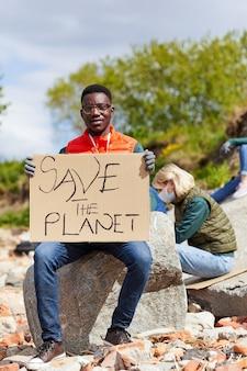 プラカードを持って、屋外の石の上に座ってカメラを見ているアフリカの若い男の肖像画