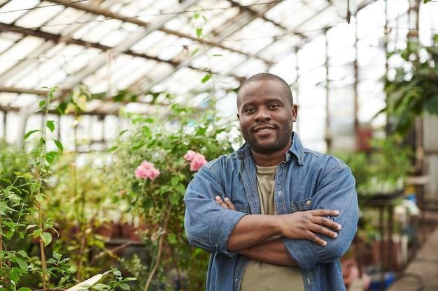 温室に立っている間カメラに微笑んでアフリカの若い男の肖像画