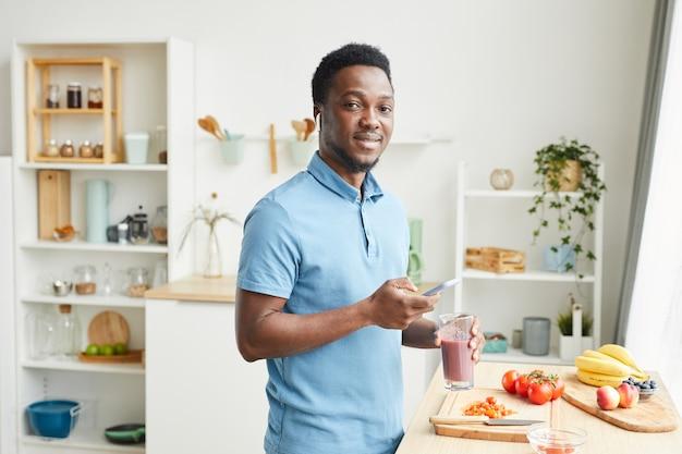 Портрет африканского молодого человека, улыбающегося, пьющего сок и использующего свой мобильный телефон на домашней кухне