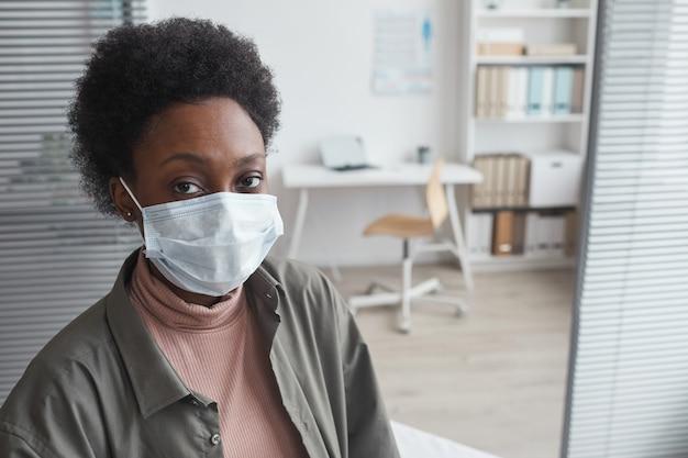 医者のオフィスに座っている間カメラを見ている保護マスクのアフリカの若い女性の肖像画