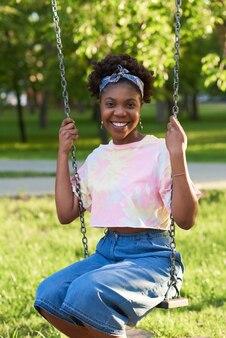 公園でブランコに座ってカメラに笑みを浮かべてアフリカの若い女性の肖像画
