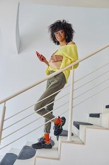 階段でスマートフォンを保持しているメガネとベルトバッグを持つアフリカ系アメリカ人の女性の肖像画