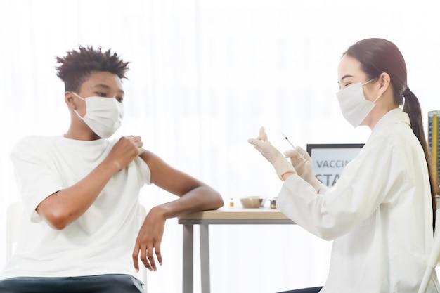 손 간호사가 주입하는 코비드 백신을 받는 동안 보고 있는 아프리카계 미국인 남자의 초상화