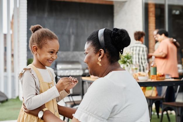 屋外のパーティーコピースペースでかわいい女の子と話しているアフリカ系アメリカ人の女性の肖像画