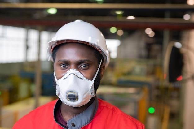 Портрет афро-американского строителя в респираторе и каске, стоящего на строительной площадке