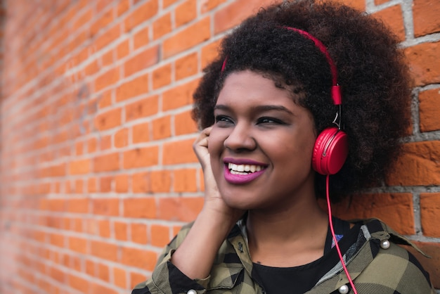 笑みを浮かべて、レンガの壁にヘッドフォンで音楽を聴くアフロアメリカンのラテン女性の肖像画。屋外。