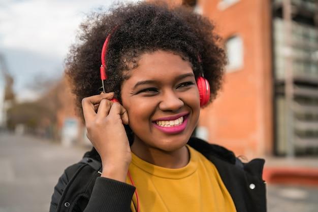 笑顔で通りでヘッドフォンで音楽を聴いているアフリカ系アメリカ人女性の肖像画。屋外。