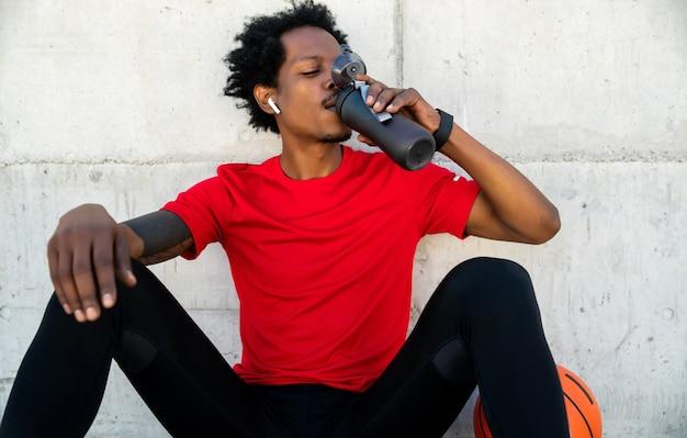 屋外で運動した後、水を飲むアフロアスリートの男性の肖像画。スポーツと健康的なライフスタイル。