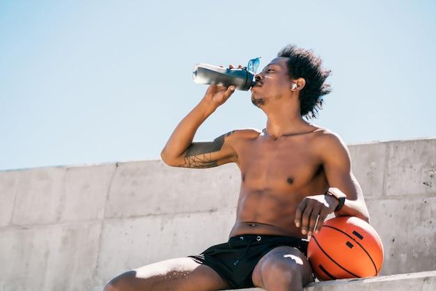 아프리카 선수 남자 식 수와 야외에서 농구 공을 들고의 초상화. 스포츠와 건강한 라이프 스타일.