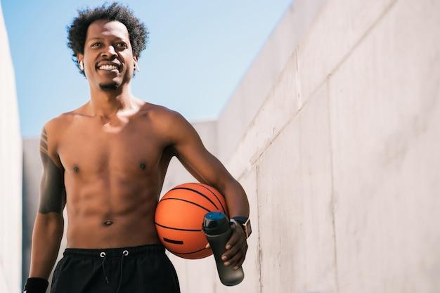 バスケットボールのボールを保持し、屋外でトレーニングした後にリラックスしたアフロアスリート男性の肖像画。スポーツと健康的なライフスタイル。