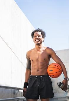バスケットボールのボールを保持し、屋外でトレーニングした後にリラックスしたアフロアスリートの男性の肖像画。スポーツと健康的なライフスタイル。