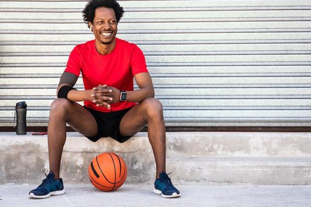 バスケットボールのボールを保持し、屋外に座ってトレーニング後にリラックスしたアフロアスリート男性の肖像画。スポーツと健康的なライフスタイル。